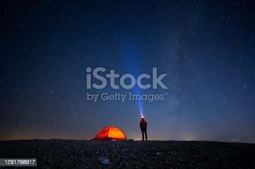 mountaineer and camping tent under the stars at night