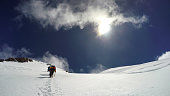 Mountaineer climbs snowfield on a sunny day high on a mountain