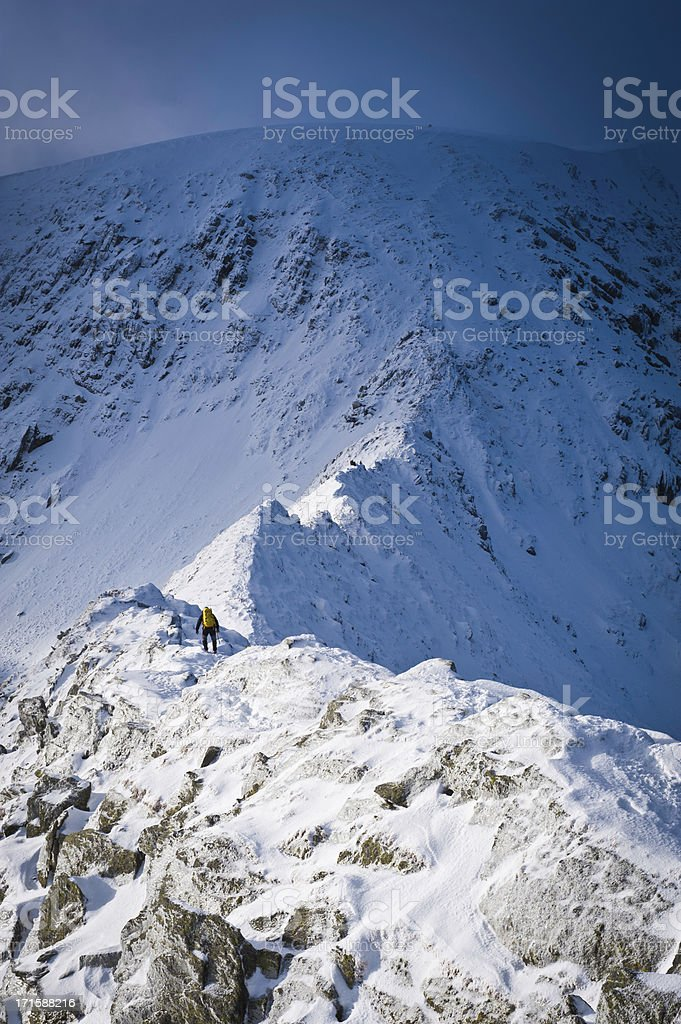 Mountaineer crossing snowy Striding Edge winter Lake District Cumbria UK royalty-free stock photo