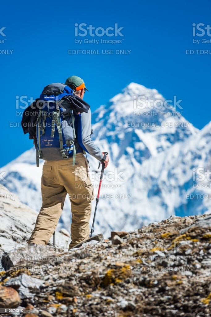 Mountaineer hiking mountain pass below Mt Everest peak Himalayas Nepal stock photo
