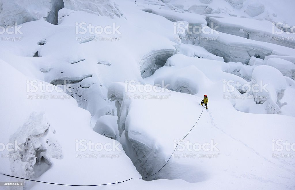 Mountaineer in snow trying to find a way around crevasses stock photo