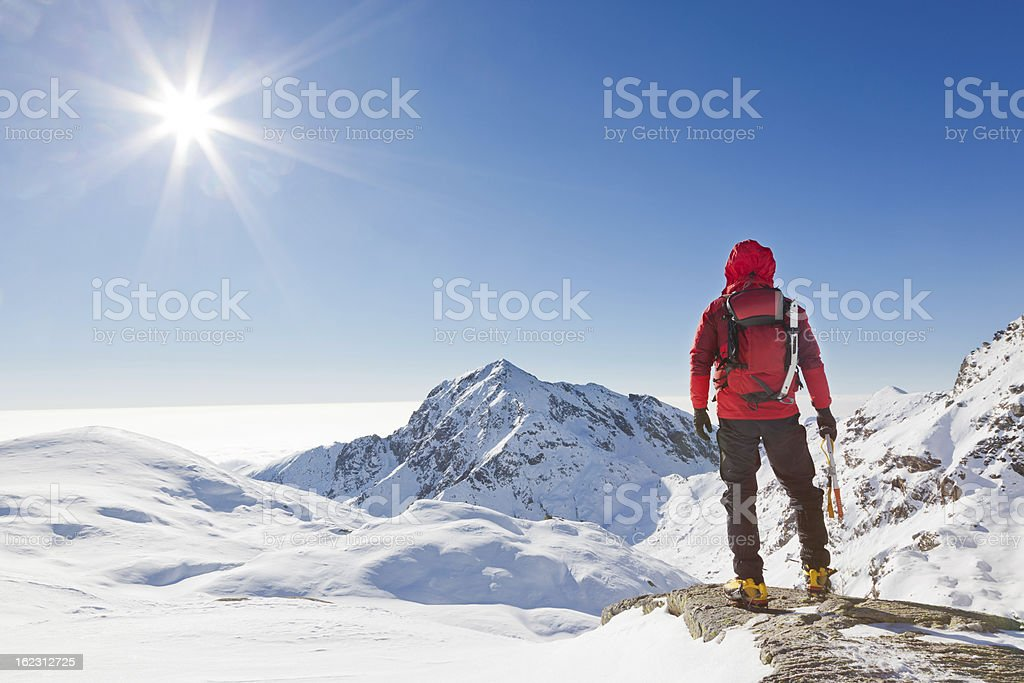 Mountaineer looking at a snowy mountain landscape stock photo