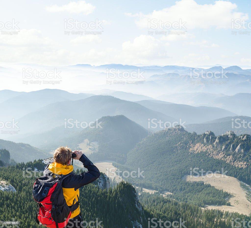 Mountaineer looking over the hills through  binoculars stock photo