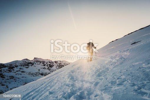 Mountaineer man climbing to the peak mountain on winter at shining sunset