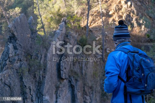 Rear view of a backpacker man observing a rocky landscape