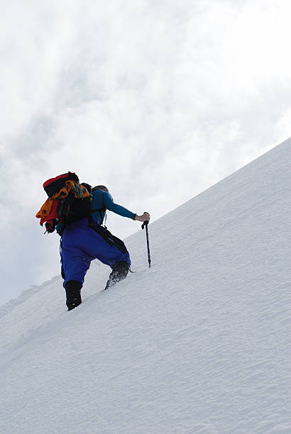 mountaineer on summit ascent in fresh snow stock photo