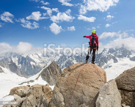 istock Mountaineer on top of the mountain pointing towards the Alps 538036987
