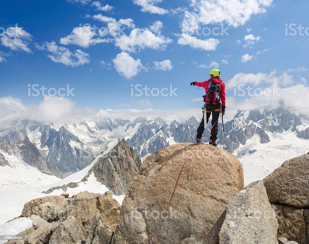 Bergsteiger auf dem Berg zeigt auf die Alpen – Foto