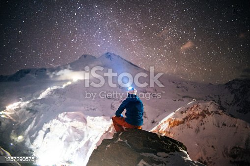 He looks up to a starry sky, shining his headlamp toward snowy mountain range