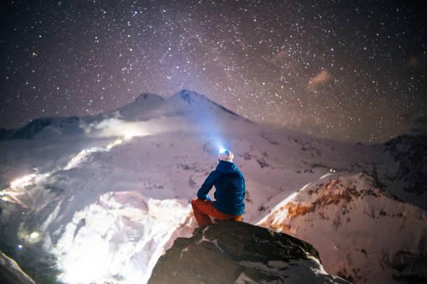 Mountaineer relaxes on mountain pinnacle at night stock photo