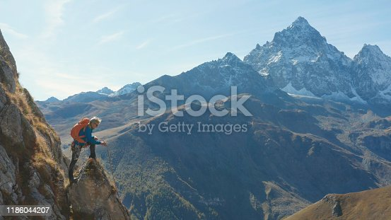603993820 istock photo Mountaineer relaxes on mountain slope 1186044207