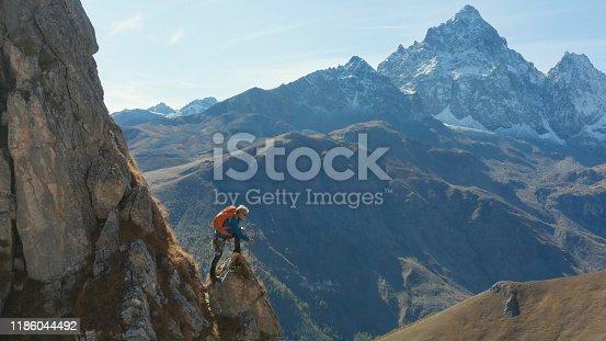 603993820 istock photo Mountaineer relaxes on mountain slope 1186044492