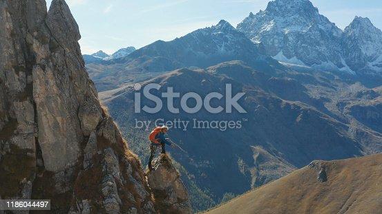 603993820 istock photo Mountaineer relaxes on mountain slope 1186044497