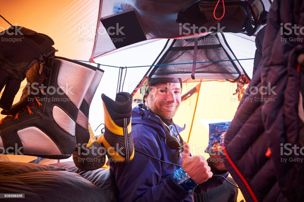 Mountaineer sitting in the entrance of a tent. stock photo