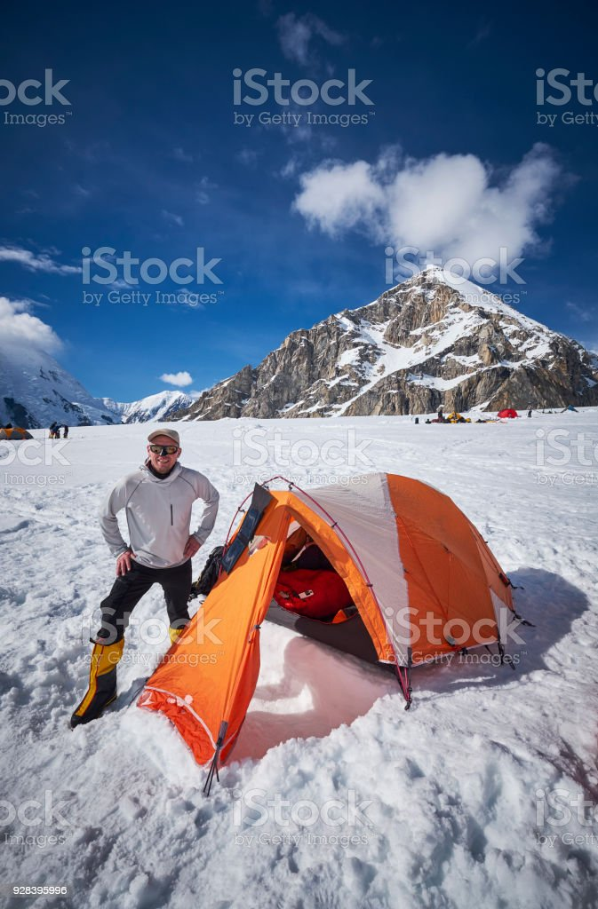 Mountaineer standing in front of his tent on Denali stock photo