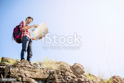 istock Mountaineer standing on a mountain peak with the map 546009454