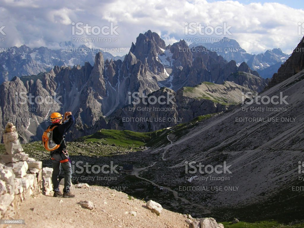 Mountaineer standing on the Path High over Valley and Taking a Photo of Mountains. stock photo