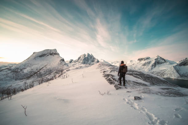 Mountaineer standing on top of snowy mountain stock photo