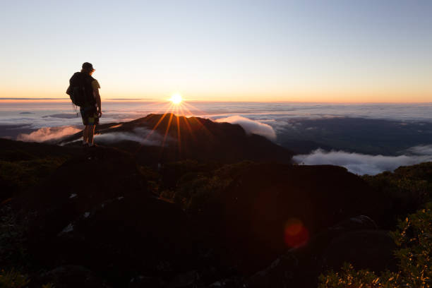 A Mountaineer Watches the Sun Rise Above the Clouds From a High Vantage Point stock photo