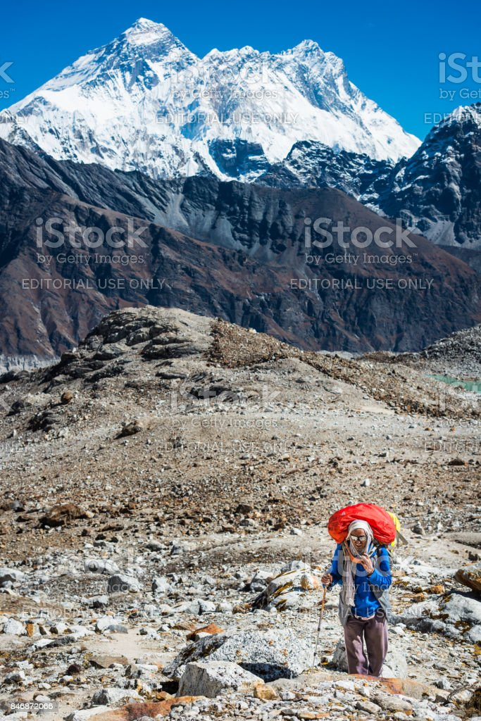 Mountaineer with heavy pack hiking below Mt Everest Himalayas Nepal stock photo