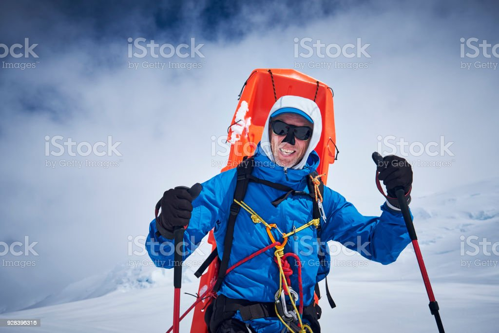 Mountaineer with sledge on his back coming down on Denali. stock photo