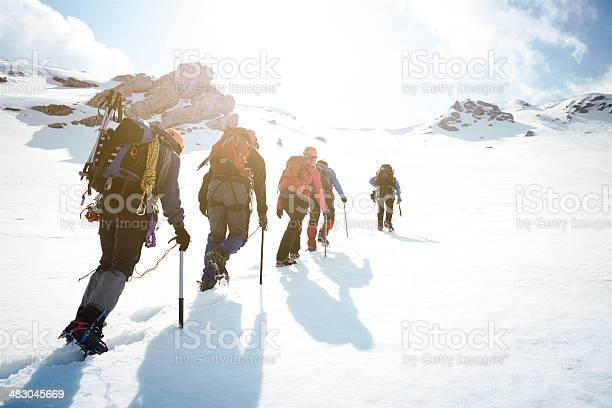 Group of mountaineers walking trough the mountains covered with snow.