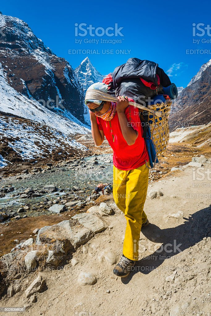 Mountaineering sherpa porter carrying doko basket along trail Himalayas Nepal stock photo