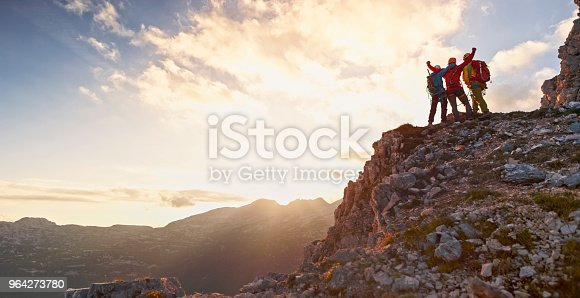 Rear view of male and female mountaineers celebrating victory on top of mountain at sunset.
