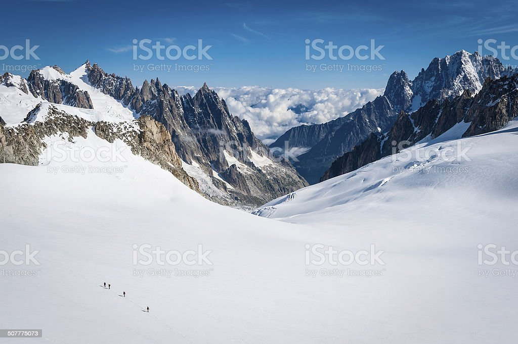 Mountaineers climbing across snow field between jagged mountain peaks Alps stock photo