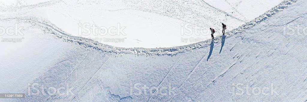 Mountaineers climbing along snow ridge Alps panorama stock photo