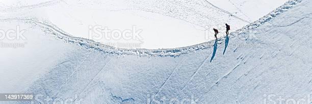 Photo of Mountaineers climbing along snow ridge Alps panorama