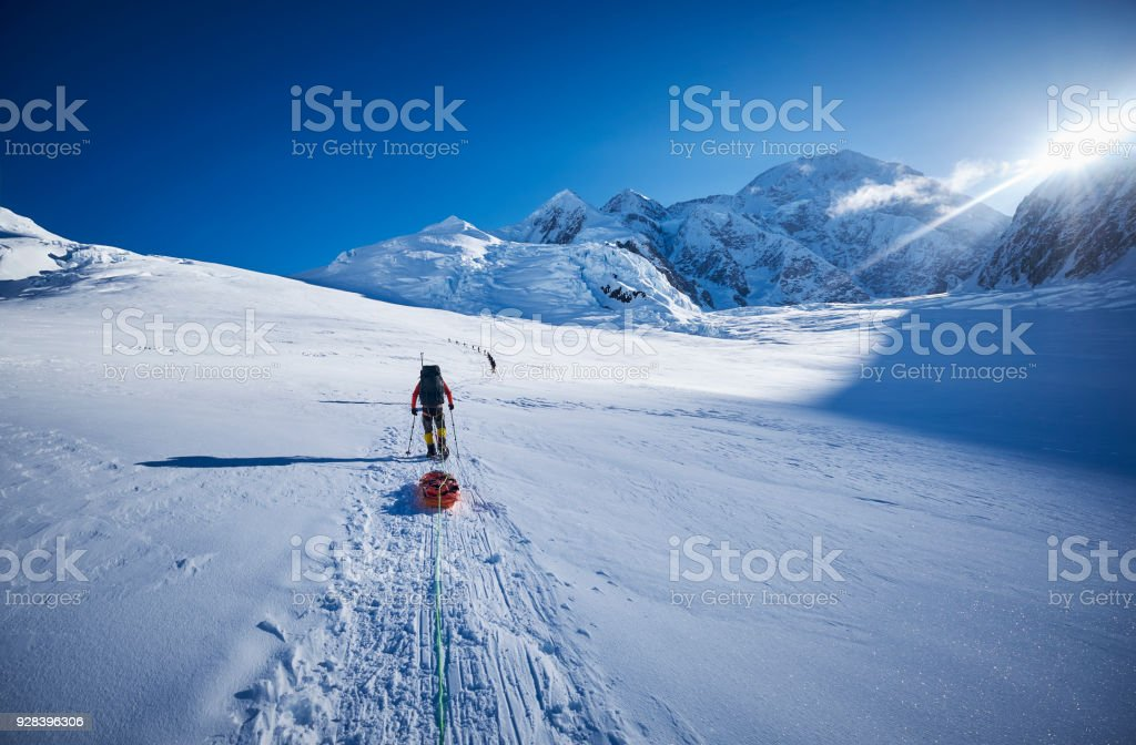 Mountaineers climbing Denali pulling a sled. stock photo
