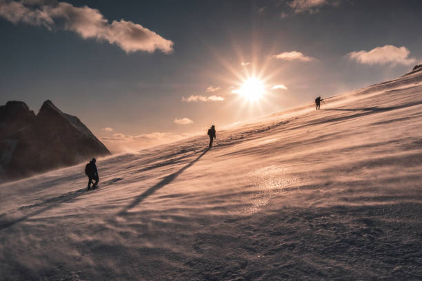Mountaineers climbing in blizzard on snowy hill at sunset stock photo