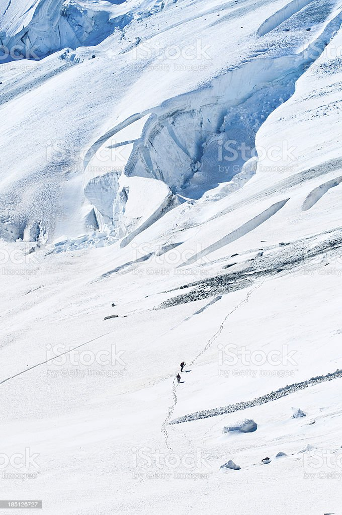 Mountaineers crossing snowy glacier wilderness Alps royalty-free stock photo