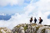 Mezica, Slovenia - August 15, 2009: Three mountaineers on top of Peca mountain. Peca is a mountain in the Karavanke Mountains on the SlovenianaaAustrian border. One mountaineer pointing to an Austrian city Bleiburg.