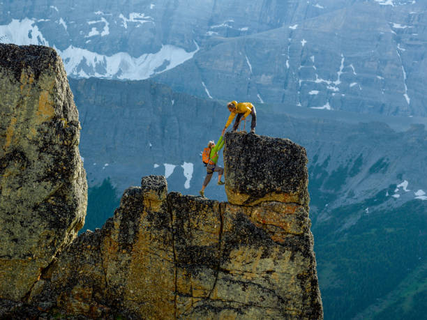 mountaineers scale rocks steps on cliff with rope - alpinismo foto e immagini stock
