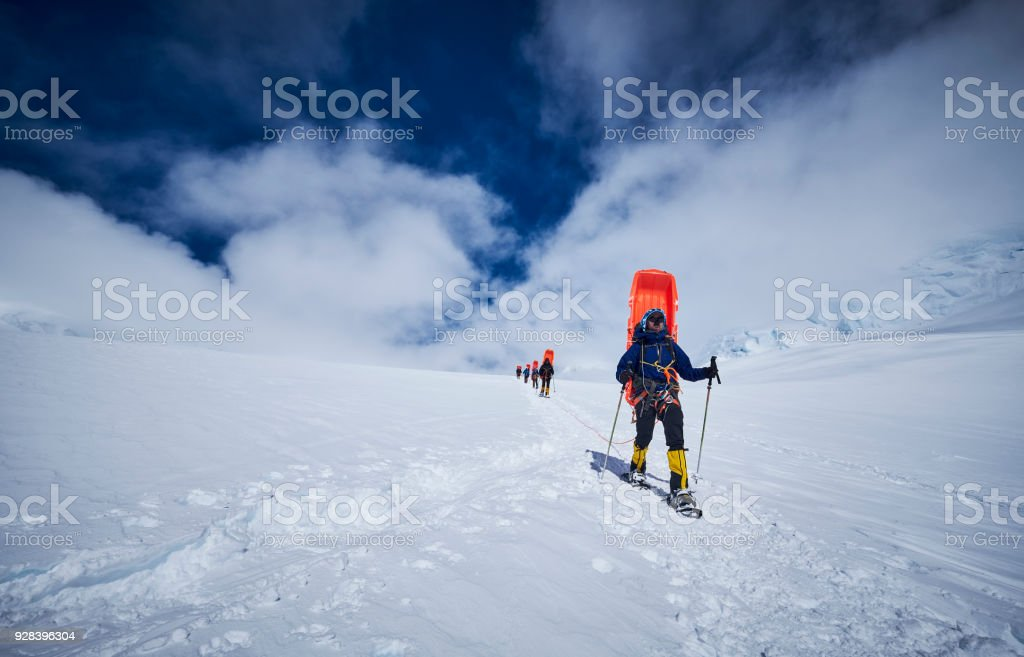 Mountaineers with sledge on his back coming down on Denali. stock photo