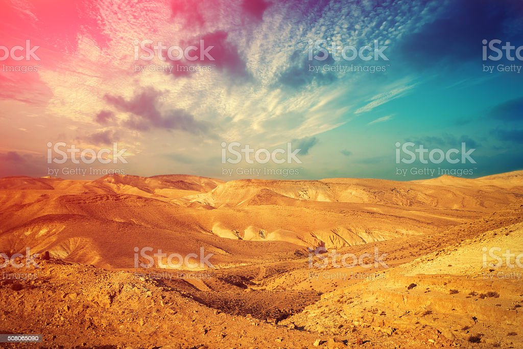 Mountainous desert with colorful cloudy sky stock photo
