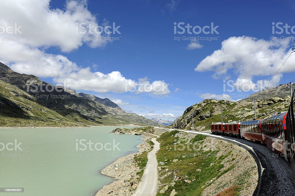 Mountainous landscape with bernina express passing through stock photo