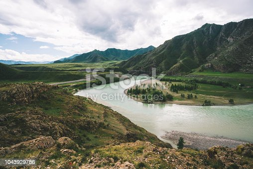 Mountainous river in highlands at overcast weather. Rocky cliff above fast water stream under cloudy sky. Giant mountains. Amazing atmospheric landscape from above.