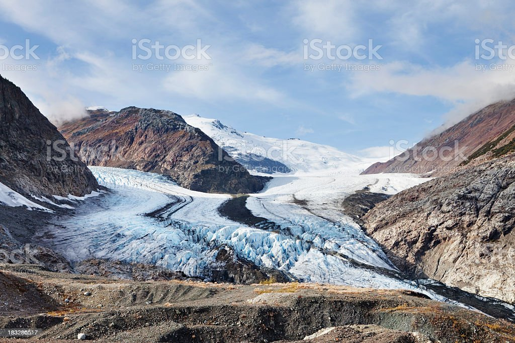 Mountainous terrain with snow and blue cloudy sky stock photo