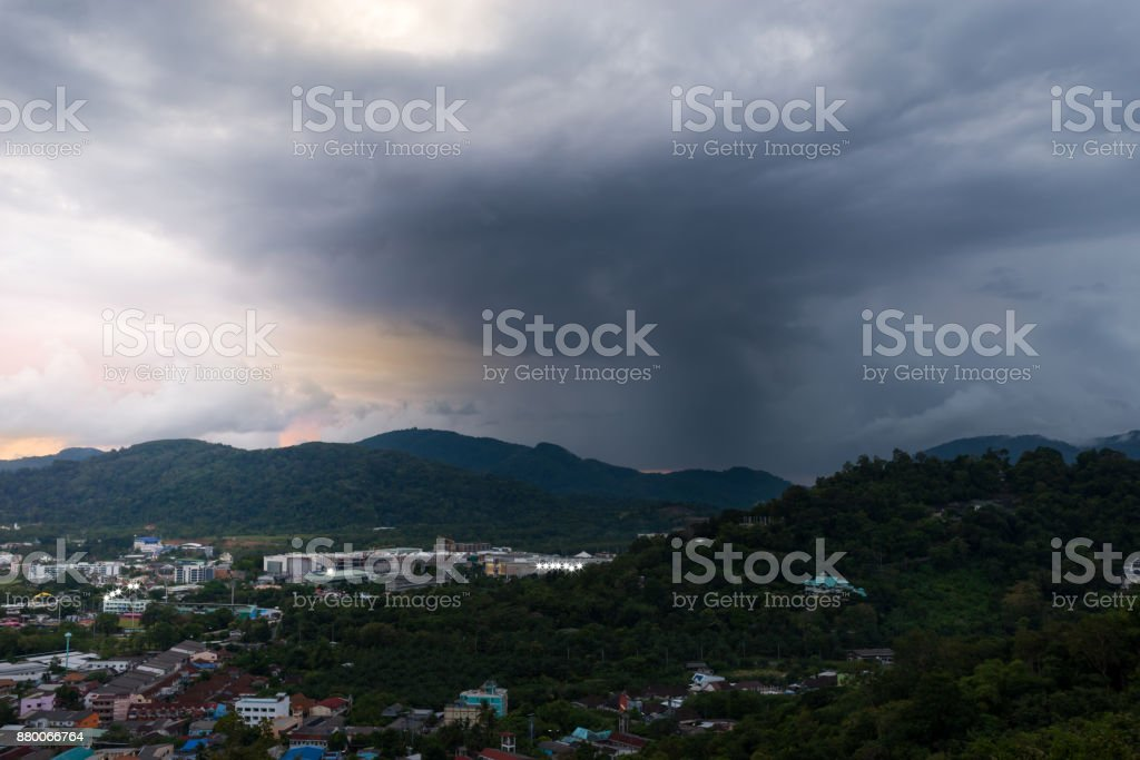 Mountains and city shrouded by storm clouds at sunset. stock photo