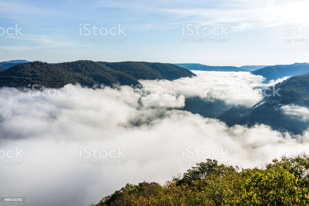 Mountains and fog, mist clouds in morning floating above forest trees, covering, blanketing valley in Grandview Overlook, West Virginia stock photo