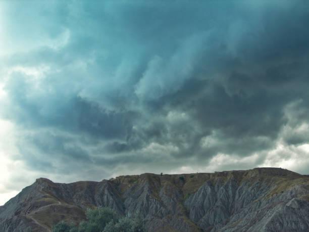 Montanhas e céu com nuvens escuras na tempestade - foto de acervo