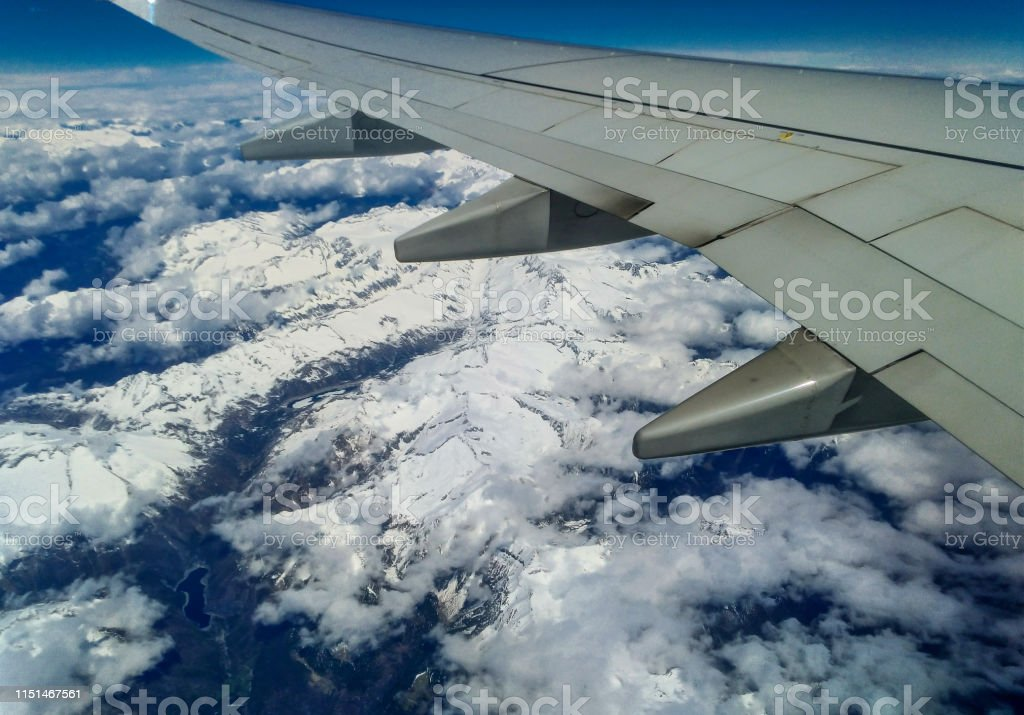 Mountains and white snow on the tops under the wing of the aircraft...