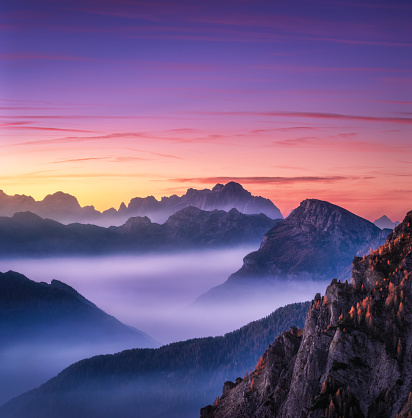 istock Mountains in fog at beautiful sunset in autumn in Dolomites, Italy. Landscape with alpine mountain valley, low clouds, trees on hills, purple sky with clouds at dusk. Aerial view. Passo Giau. Nature 1128740646