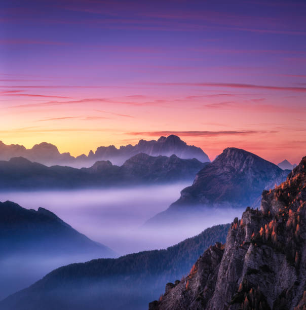 mountains in fog at beautiful sunset in autumn in dolomites, italy. landscape with alpine mountain valley, low clouds, trees on hills, purple sky with clouds at dusk. aerial view. passo giau. nature - den belitsky foto e immagini stock