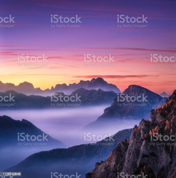 Photo of Mountains in fog at beautiful sunset in autumn in Dolomites, Italy. Landscape with alpine mountain valley, low clouds, trees on hills, purple sky with clouds at dusk. Aerial view. Passo Giau. Nature