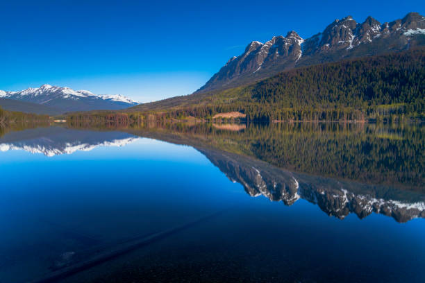 Mountains in morning light reflected in calm lake waters stock photo