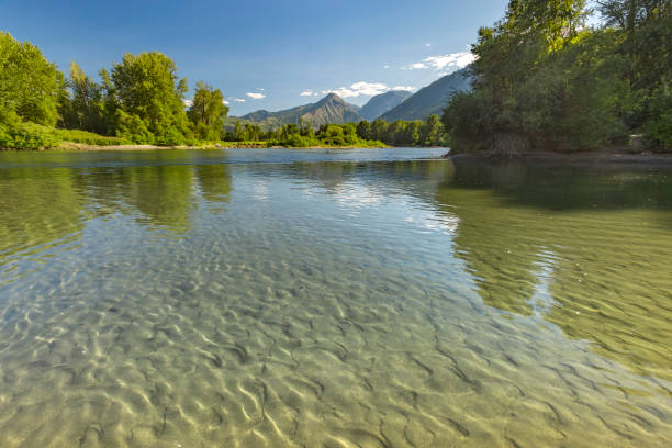 mountains in the background of the reflective river of wenatchee in leavenworth washington - leavenworth washington stock photos and pictures